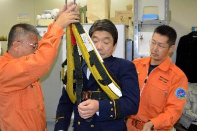 男性を救助時につり上げ用具が外れた状況を説明する静岡市消防局幹部ら。ヘリコプターに収容しようと男性の胸部にベルトを巻き付け、つり上げたが、ずり落ちたという=2013年12月2日、静岡市役所