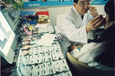 整形手術を受けた女子大生の術後経過を診る医師の横に並べられた目の写真標本