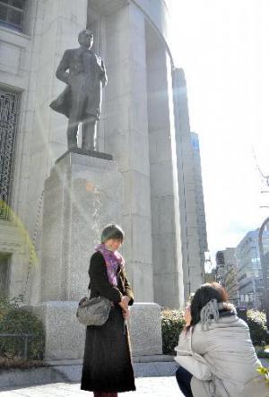 大阪取引所の五代友厚像の前で記念撮影をするファン=2016年1月22日、大阪市中央区