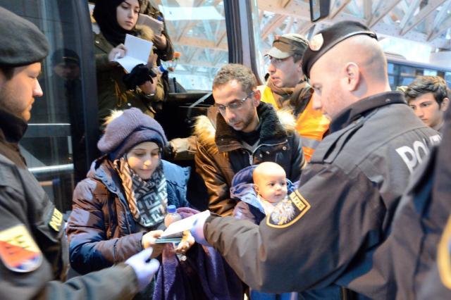 バスから降りて書類のチェックを受ける若い難民の夫婦。赤ちゃんを抱いていた=オーストリア南部カラワンケン・トンネル、喜田尚撮影
