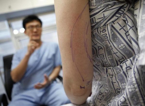 オーストラリアから美容整形のために韓国へ来た女性に施術の説明をする医師=2011年1月4日、ロイター