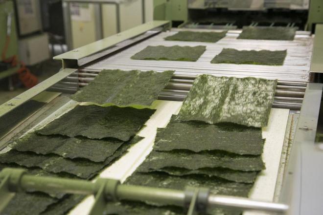 のりたまの製造過程。海苔を焼いてカットする