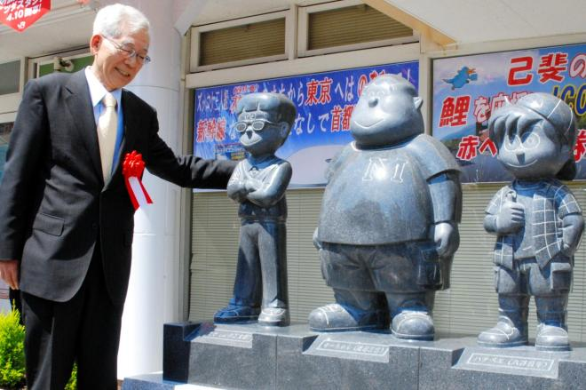 自らがモデルという「ハカセ」のモニュメントに手をかける作者の那須正幹さん=2009年4月11日、広島市西区のJR西広島駅前で