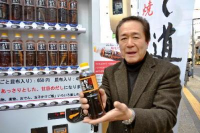 ペットボトルに入った「だし道楽」を持つ二反田博文社長=2013年12月24日、広島市中区