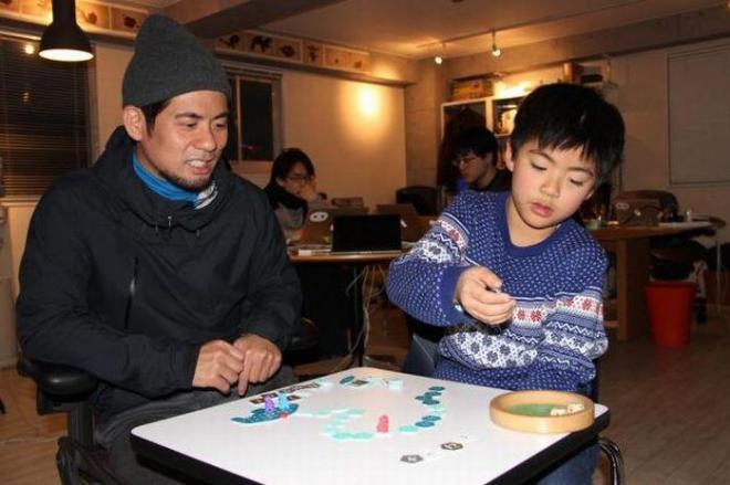 ゲームデザイナーの佐々木隼さん(左)と、長男の吾朗くん。第1回「ゲームマーケット大賞」に輝いた「海底探険」を発案した