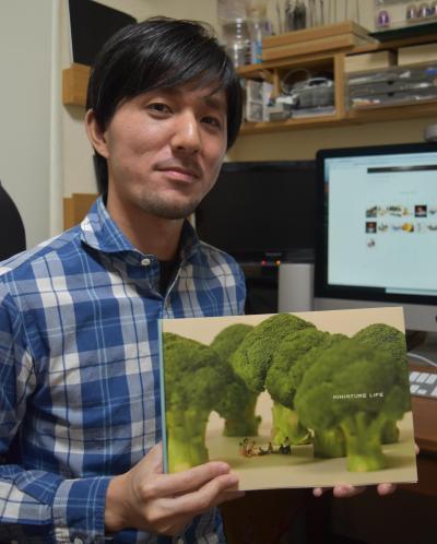 1冊目の写真集を持つ田中達也さん=鹿児島市