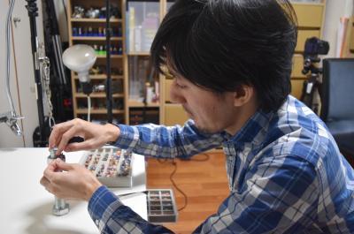 約1.5センチの人形を器用にナットに乗せていく田中さん=鹿児島市