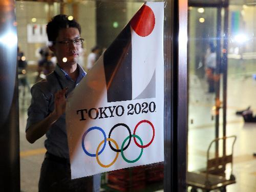 【エンブレム】都庁玄関で、使用中止が決まった東京五輪エンブレムのポスターをはがす東京都職員=2015年9月1日
