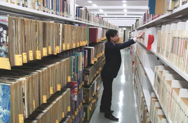 国会図書館関西館の書架。手前左の雑誌は、背表紙が見えるよう縦置きだったのを、背表紙を上にする形にし、スペースを有効活用している=京都府精華町(2015年)