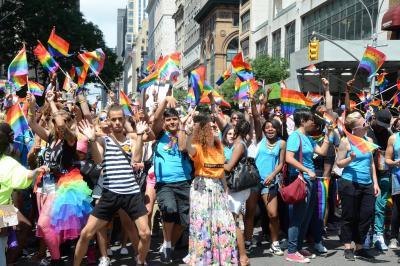 性的多様性の象徴のレインボーフラッグを振りながら、ニューヨークの五番街を行進する「プライド行進」の参加者たち=2015年6月
