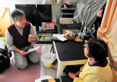 仮設住宅で被災者の話に耳を傾ける岩手大の麦倉哲教授(左)。被災者を定期的に訪れ、調査とともに見守りを続けている=2015年10月16日、岩手県大槌町