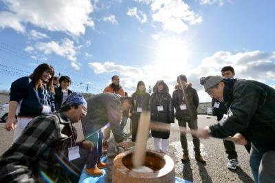 仮設住宅の住民とともに餅をつくボランティアたち=2015年12月19日、宮城県名取市、日吉健吾撮影