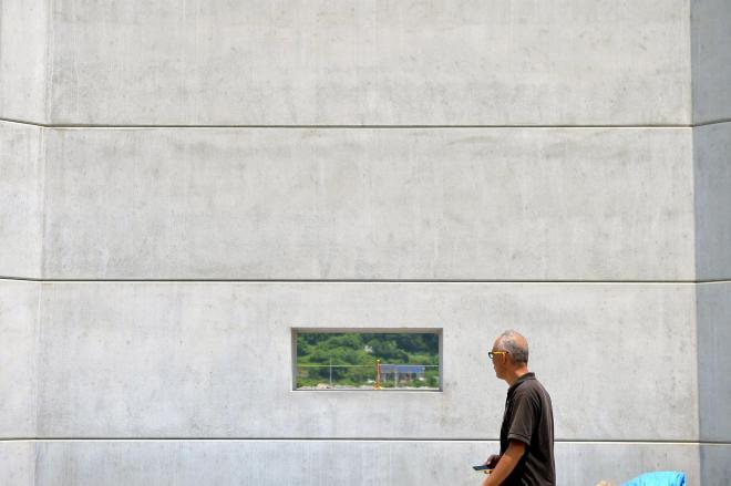 気仙沼港の南側に建設中の、窓のついた防潮堤=2015年7月30日、宮城県気仙沼市