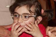 支援チームの女性から贈られたメガネをかける国内避難民の子ども=アゼルバイジャンのバクーで