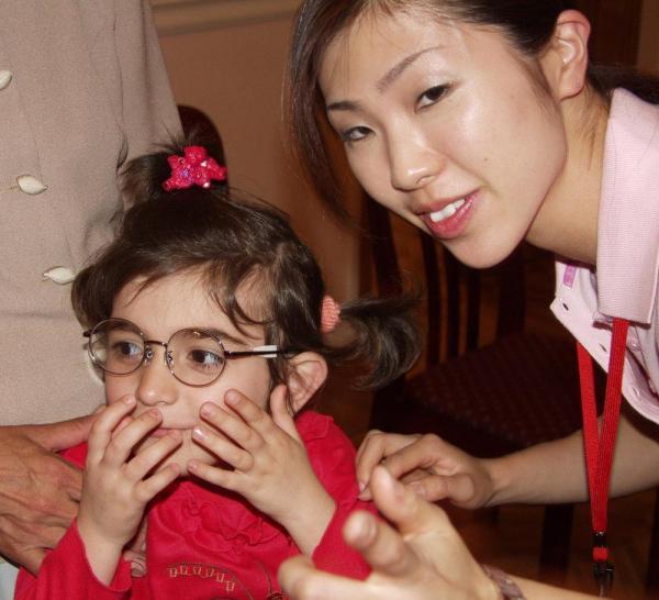 支援チームの女性から贈られたメガネをかける国内避難民の子ども=アゼルバイジャンのバクーで(富士メガネ提供)