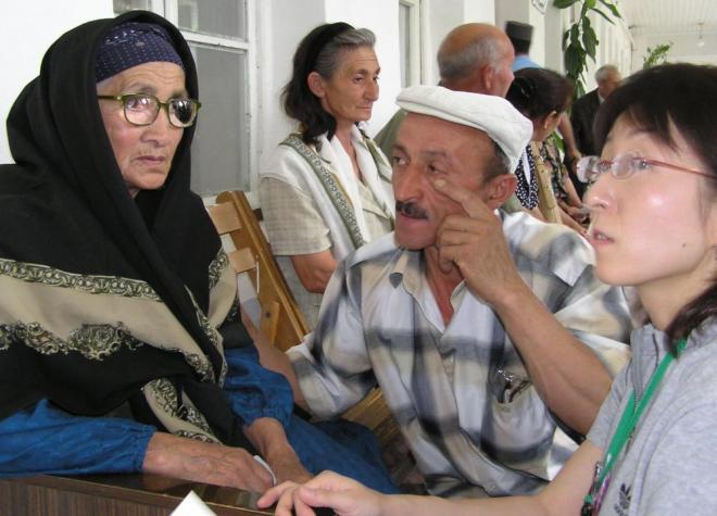 視力検査を終え、老眼鏡をかけるお年寄りの女性(左)=ハジガブールの医療施設で(2005年)