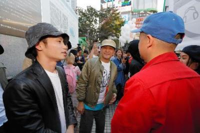 抗議行動終了後、ステージ裏でラップグループ「スチャダラパー」のメンバーと談笑する学生団体「SEALDs」の奥田愛基さん(左)=2015年10月18日