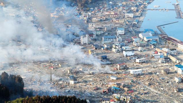 津波に襲われ、煙を上げて燃える市街地=2011年3月12日、岩手県山田町、本社ヘリから、上田潤撮影