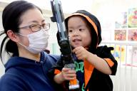 母の菜津美さんが手作りした「仮面ライダーゴースト」の服を着て病室で遊ぶ矢野秀虎くん=東京都府中市、越田省吾撮影