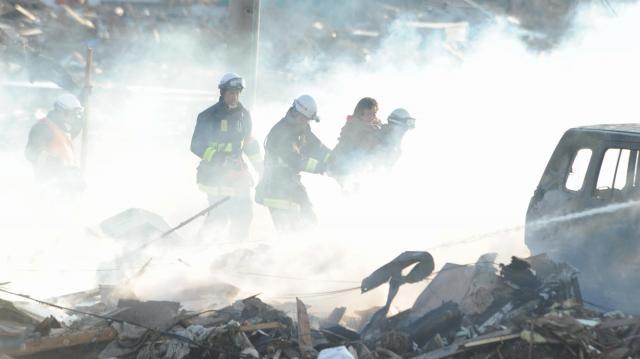 がれきの山と化した集落から消防署員らに救助される住民=2011年3月12日、宮城県名取市