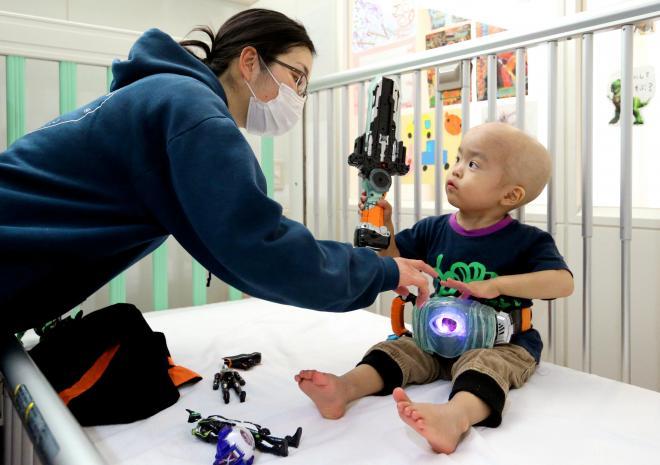 病室で母の菜津美さんを相手に、「仮面ライダーゴースト」のおもちゃで遊ぶ矢野秀虎くん=東京都府中市、越田省吾撮影