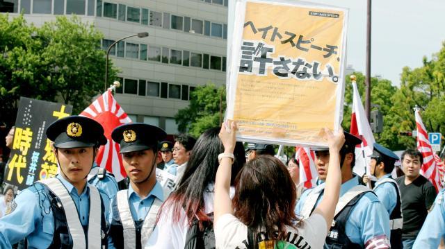 デモ参加者に向かって「ヘイトスピーチ、許さない。」のプラカードを掲げる女性=2015年5月31日、名古屋市中区