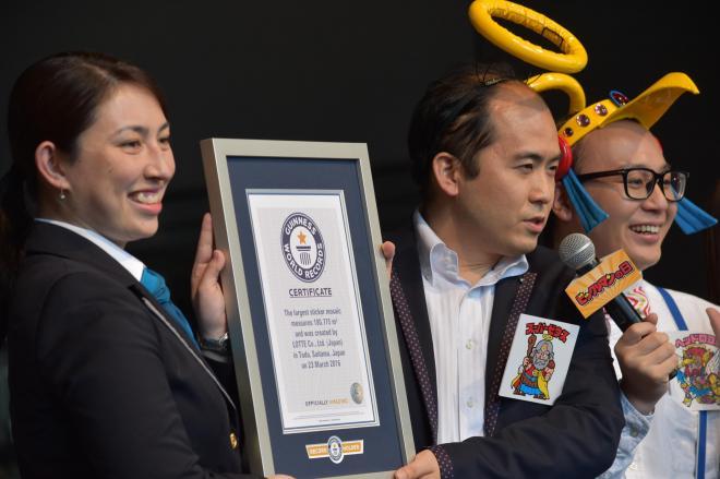 78400枚のシールで作った巨大ビックリマンシールがギネス世界記録に認定され、認定証を受け取るトレンディエンジェルの斎藤司さん(中央)