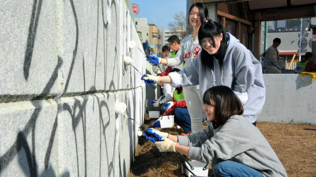 壁の落書きを消すボランティアの大学生ら