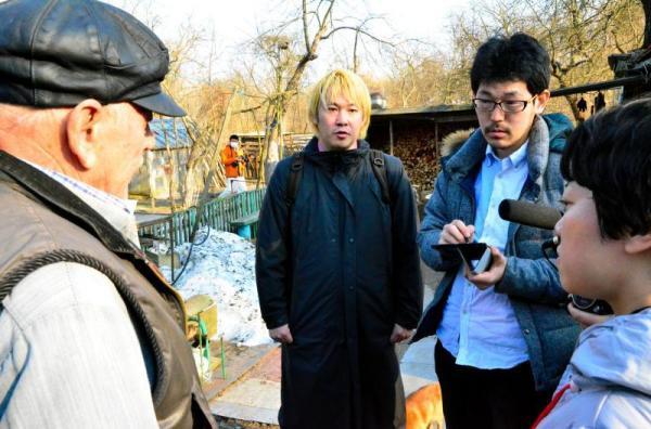 「サマショール」と呼ばれるチェルノブイリ事故後に立ち入り禁止区域内に戻って暮らす男性(左)に話を聞く津田大介さん(中央)と開沼博さん(右から2人目)=2013年4月12日、チェルノブイリ