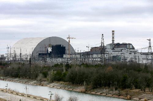 チェルノブイリ原発の「石棺」を覆う巨大なかまぼこ形の新シェルター(左)=2016年3月23日、杉本康弘撮影