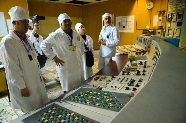 2号炉の制御室を見学する東浩紀さん(中央)と津田大介さん(左)=2013年4月12日、チェルノブイリ