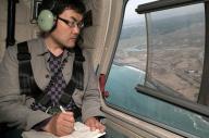 被災地を上空から眺める和合亮一さん=2013年5月18日、南相馬市沖上空で