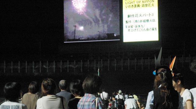 2011年8月11日、大型スクリーンに映し出された花火を見る人たち=いわき市平谷川瀬