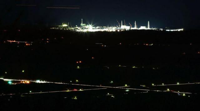 日没後、浮かび上がる東京電力福島第一原子力発電所=2015年3月12日、福島県富岡町の山中から、長時間露光、関田航撮影