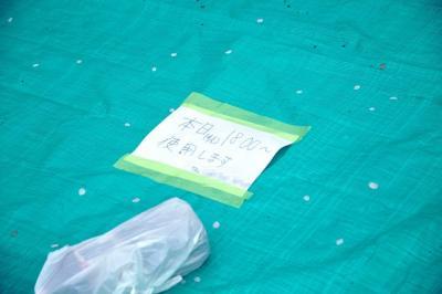 無人の場所取りシートに張られた紙。30分待ってみたが、持ち主は帰ってこなかった=4月、横浜市の掃部山公園、軽部撮影