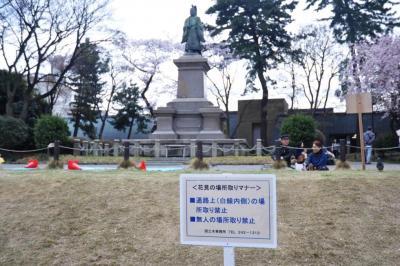 無人での場所取りなどを禁止する看板と、後ろに立つ井伊直弼像=4月、横浜市の掃部山公園、軽部撮影