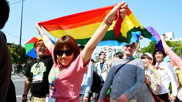 性的少数者への理解を求め、練り歩く人々。性の多様性を象徴するレインボーカラーの旗を広げる人もいた=2015年4月26日