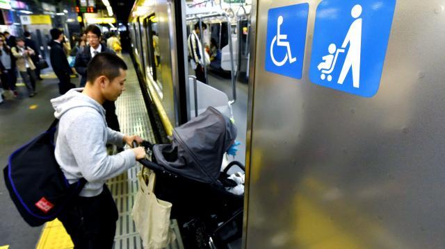 JR新宿駅でベビーカーマークがついた車両に乗り込む乗客=2015年11月20日