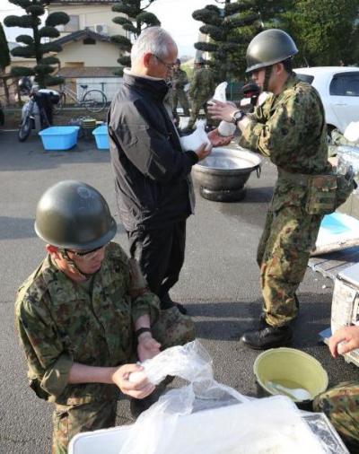 地震から一夜が明け、自衛隊員からおにぎりを受け取る被災者たち=15日午前7時8分、熊本県益城町、上田幸一撮影
