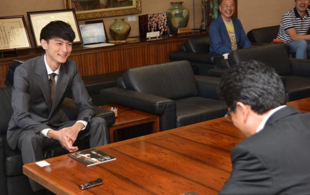 熊本市の大西市長と話し、笑顔を見せる高良健吾さん=2015年7月、熊本市役所