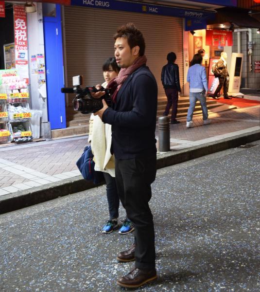 横浜駅西口で取材する上野健ディレクターと井水奈奈アシスタントディレクター(左)