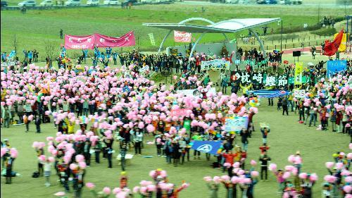 九州新幹線のCMでピンク色の飾りを持って出迎える人たち=JR九州提供
