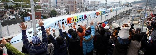 CM撮影用のカメラを載せ、7色にラッピングされた新幹線に向かって手を振る参加者たち=2011年2月20日、熊本市