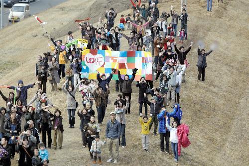 九州新幹線のCMで川の土手に集まった人たち=JR九州提供