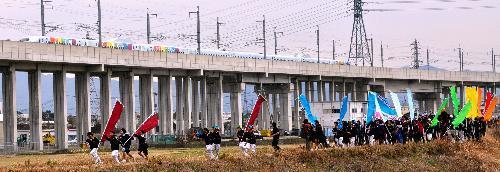 CM撮影用のカメラを載せた新幹線を、のぼりを持って追いかける参加者たち=2011年2月20日、鳥栖市蔵上町の安良川