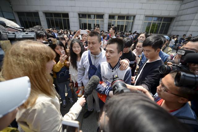 4月13日裁判所の外で取材陣に囲まれる2人