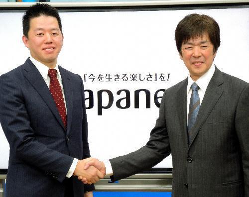 記者会見後に握手する前社長の高田明氏(右)と新社長の旭人氏=2015年1月16日