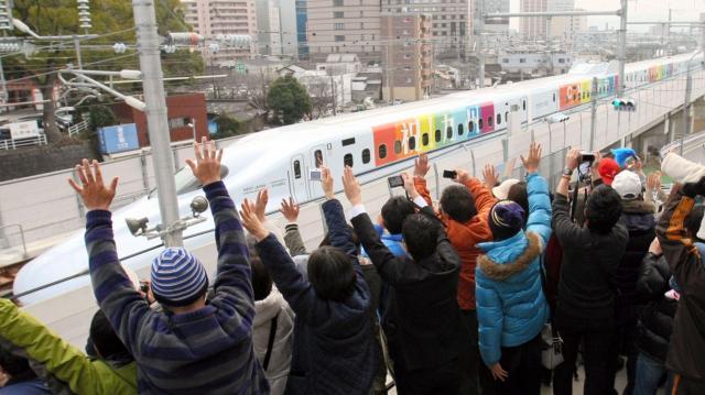 2011年2月20日、熊本市であった九州新幹線のCM撮影。参加者たちは、撮影用のカメラを載せ、7色にラッピングされた新幹線に向かって手を振った=熊本市