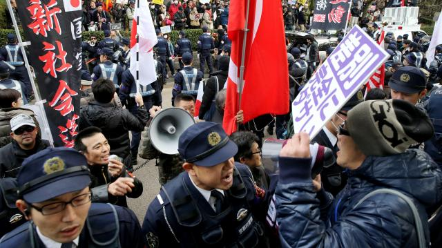 ヘイトスピーチのデモのため集まった人々(左)を出発させないように、反対する人々(右)が取り囲んだ。多数の警察官が警備し騒然とした=2014年12月7日、京都市東山区