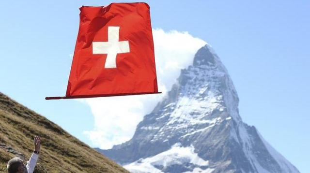 スイスのマッターホルンと国旗=ロイター
